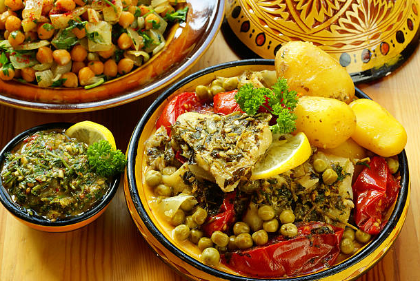 yellow-plates-of-moroccan-food-on-a-wooden-table-picture-id104734582